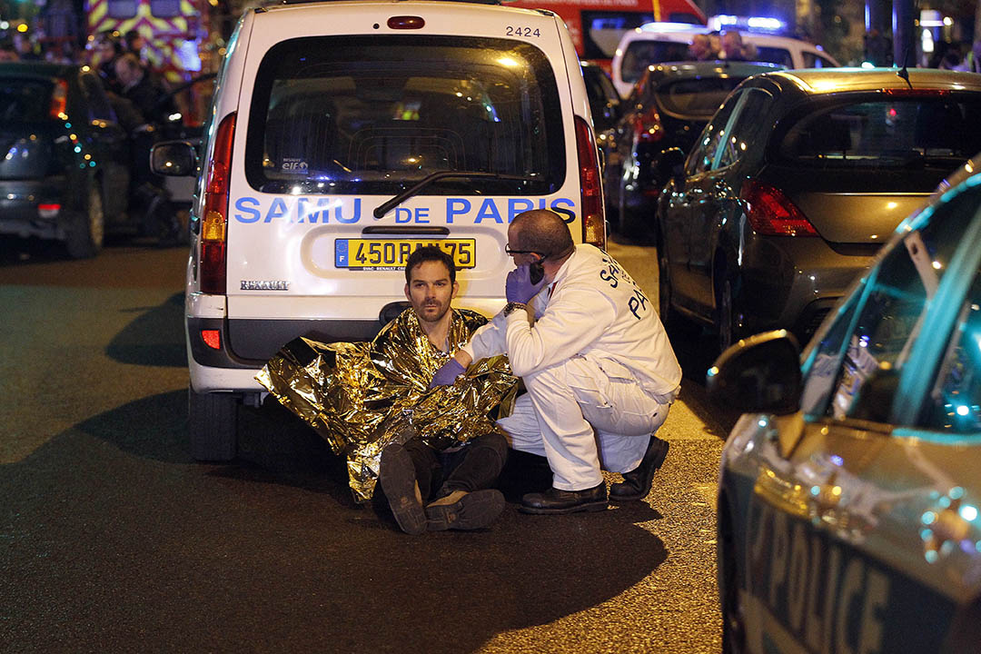 PARIS, FRANCE - NOVEMBER 13:  A medic tends to a man near the Boulevard des Filles-du-Calvaire after an attack November 13, 2015 in Paris, France. Gunfire and explosions in multiple locations erupted in the French capital with early casualty reports indicating at least 60 dead. (Photo by Thierry Chesnot/Getty Images)