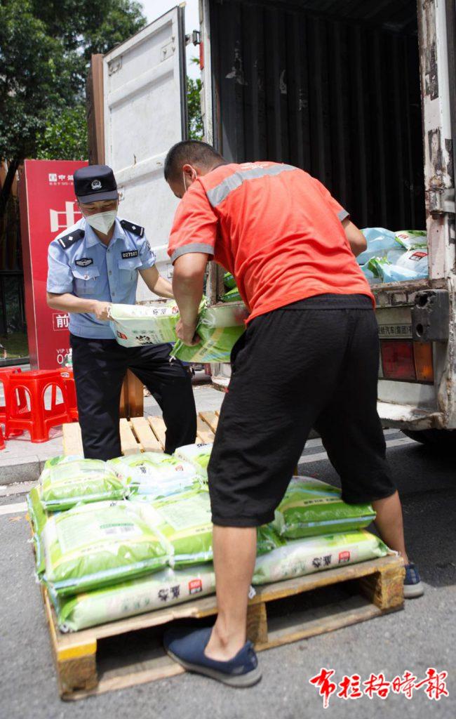 广州一封闭管理区域,民警正在帮忙搬运物资。符超军 摄